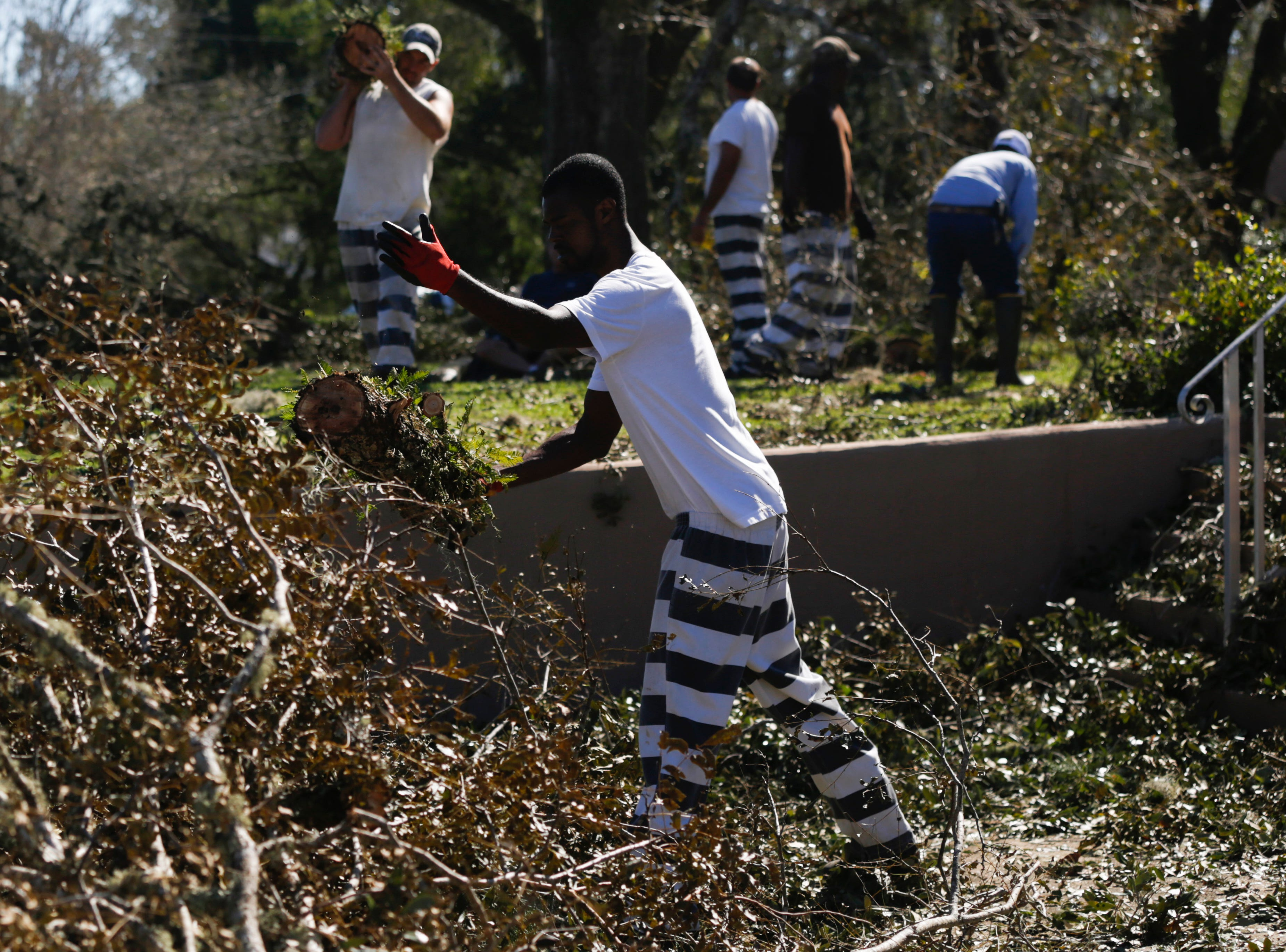 Calhoun County jail inmate Taurus Black helps to clear debris from the front of the Calhoun County Court House in Blountstown, Fla. in the aftermath of Hurricane Michael Friday, Oct. 12, 2018.