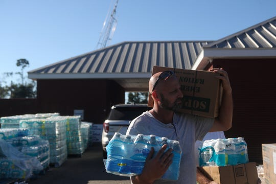 Burk Dasher carries food and water to his vehicle at the Liberty County Emergency Operations Center in Bristol, Fla. in the aftermath of Hurricane Michael Friday, Oct. 12, 2018.