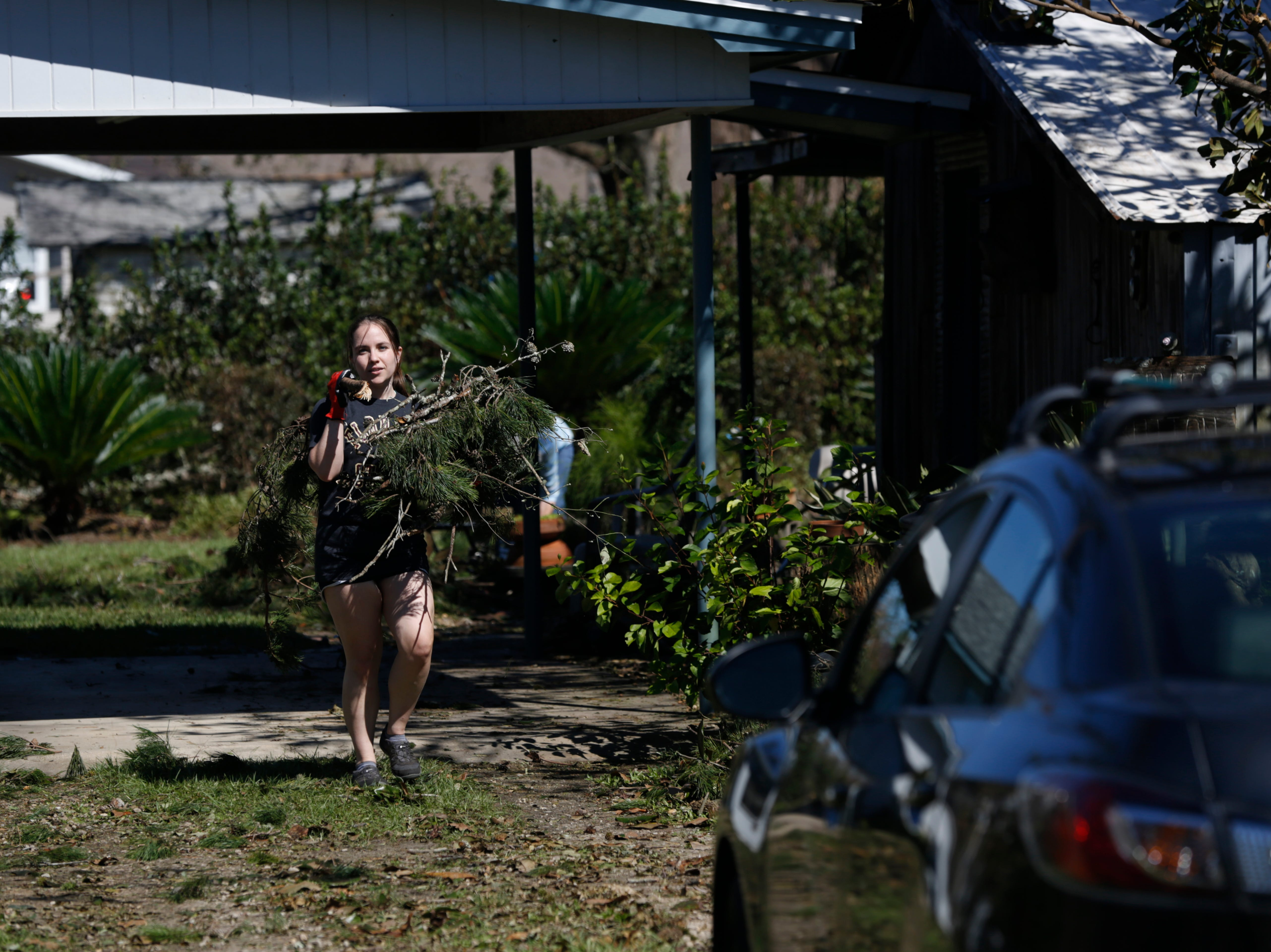 Lynn Phillips help clear branches from the yard of her boyfriend's grandparents in Blountstown, Fla. in the aftermath of Hurricane Michael Friday, Oct. 12, 2018.