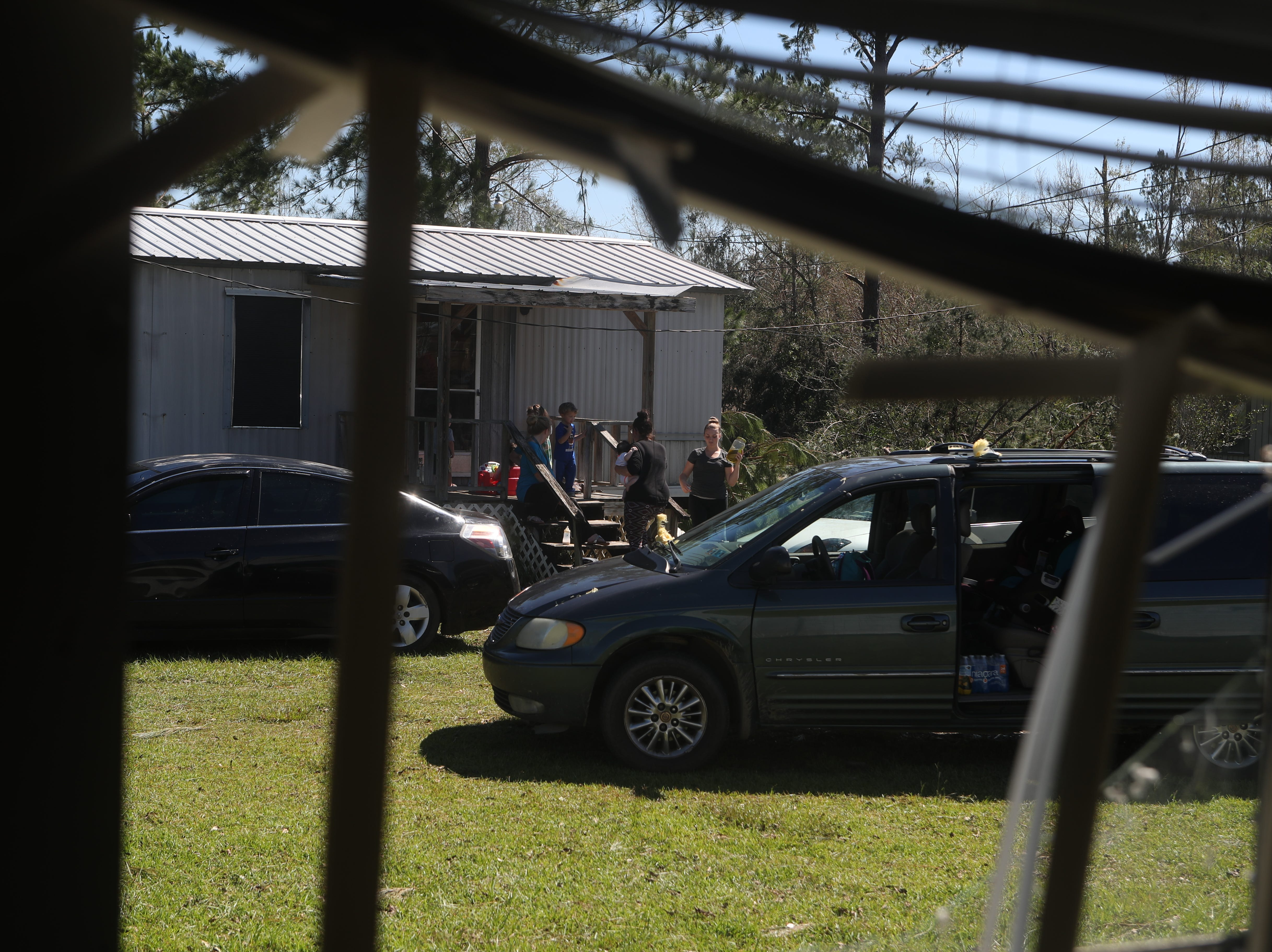 Seen from the broken window of their home, Caleb Hoffman's family sits with neighbors in Blountstown, Fla. in the aftermath of Hurricane Michael Friday, Oct. 12, 2018.