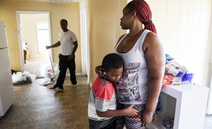 Sheila Dukes hugs her son Ezekiel, 8 as Quan Gloves mops up water from the floor of their rental house in Panama City, FL. Hurricane Michael tore the roof off, flooding the entire wooden structure.