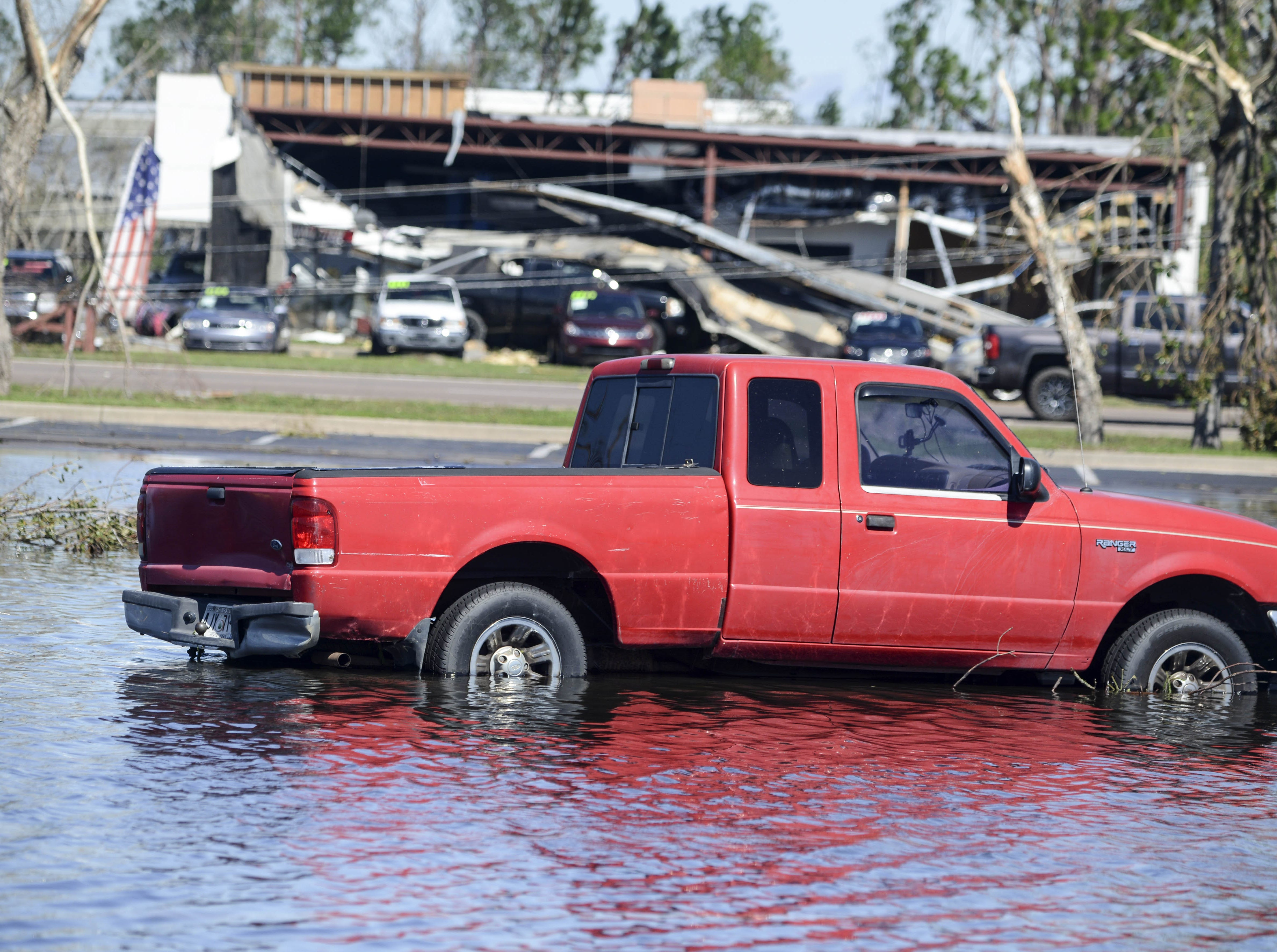 A pickup truck sits in a flooded parking lot in the Panama City Square shopping center in Panama City.