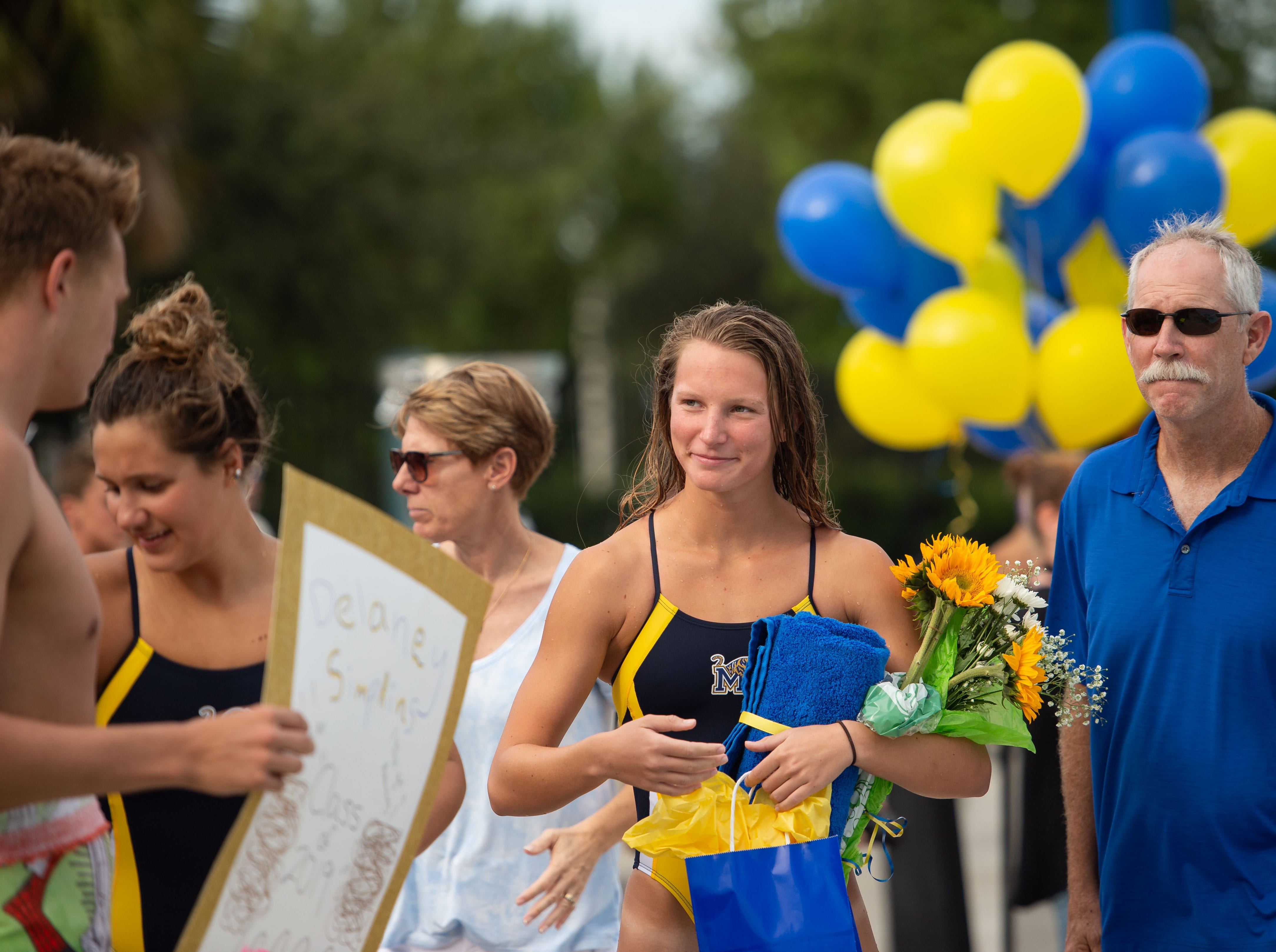 Martin County's Delaney Simpkins is honored during senior night as schools compete at the Martin County Championships high school swim and dive meet Thursday, Oct. 11, 2018, at Sailfish Splash in Stuart.