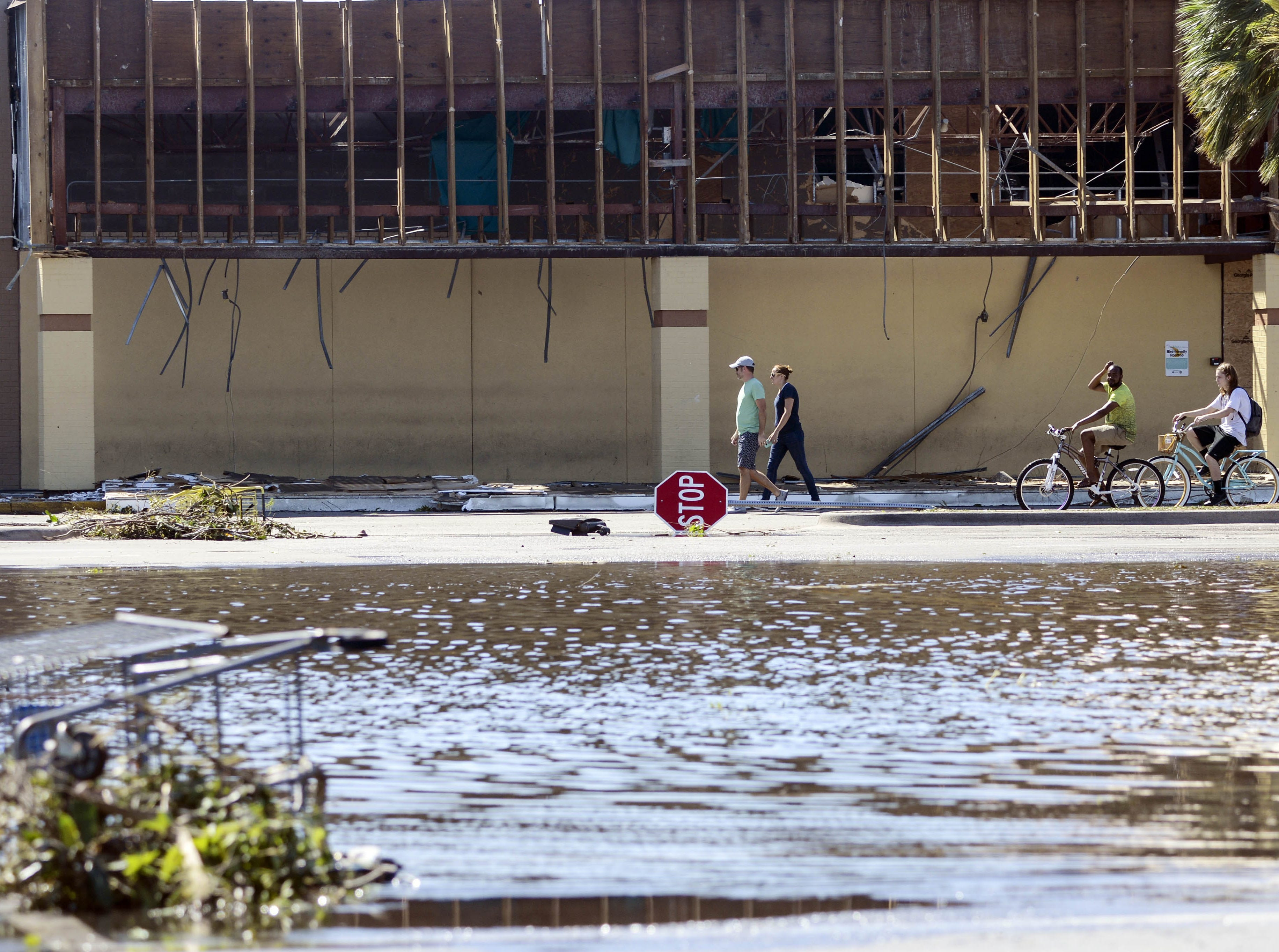Pedestrians walk and ride through a flooded parking lot in the Panama City Square shopping center in Panama City.
