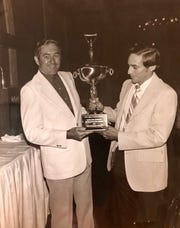 John J. Schumann Jr. (right) is presented the trophy for the Florida Press Associations' Better Newspaper Award in 1973 by an unknown man.