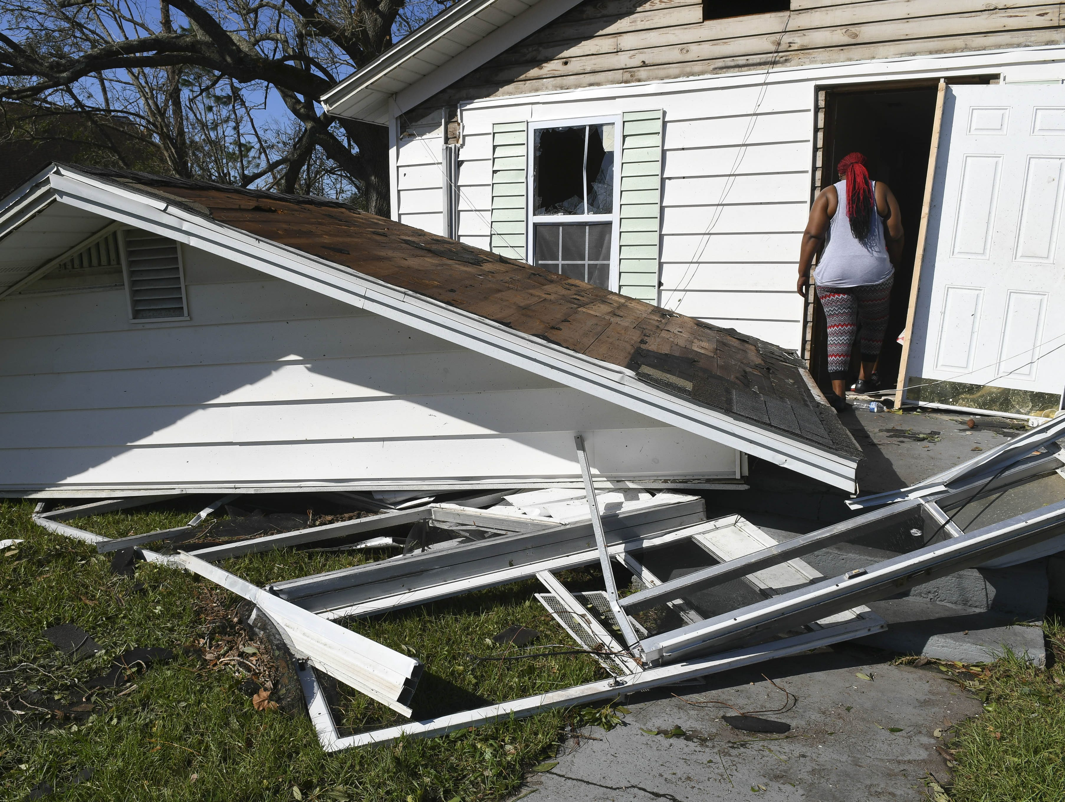 Sheila Dukes heads into what's left of her rental home in Panama City, FL Thursday. Hurricane Michael removed the front and back porches along with most of the roof.