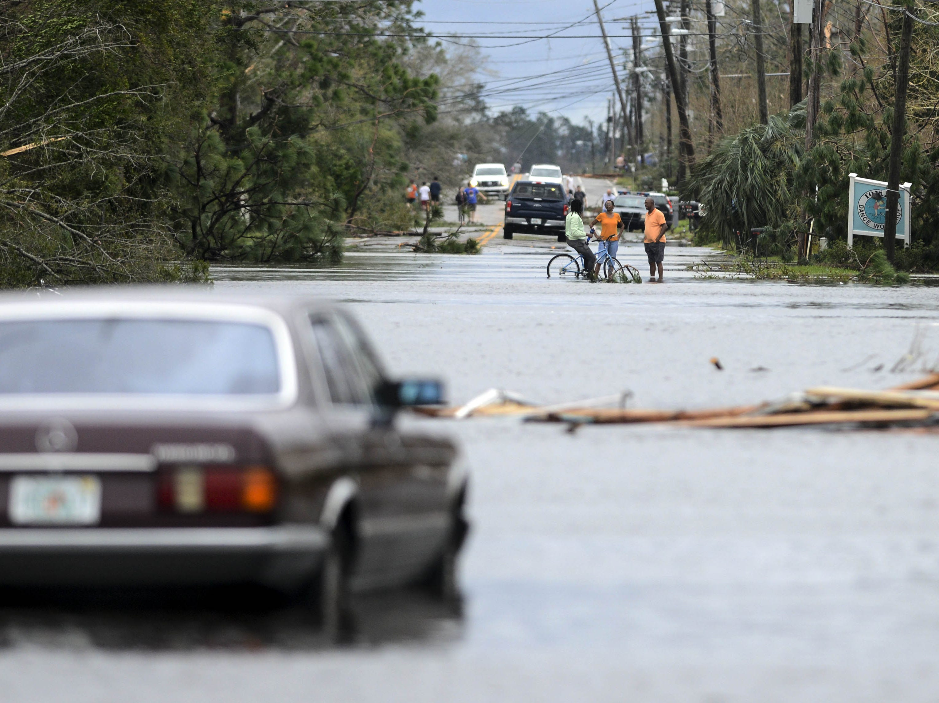 People stand in a flooded street in Panama City, FL Wednesday after Hurricane Michael.