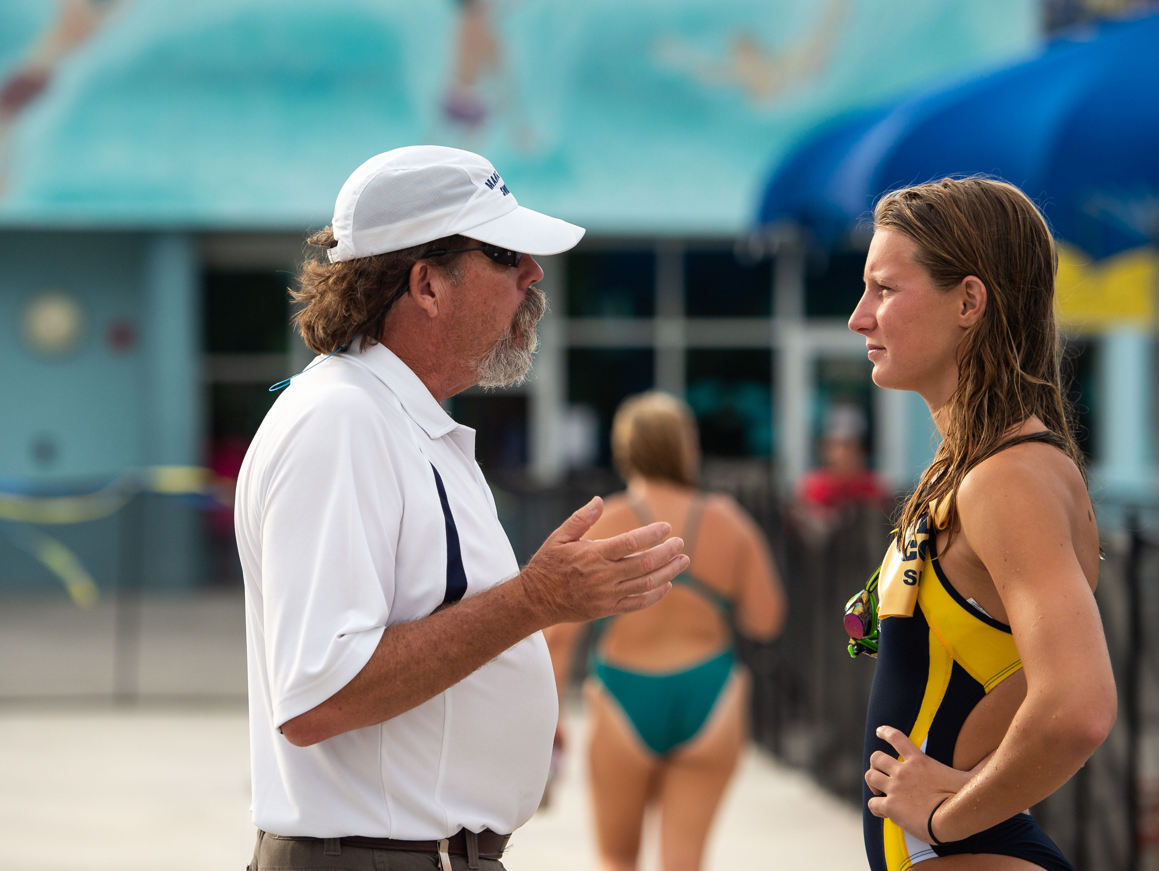 Martin County coach Jim McCombs talks with swimmer Delaney Simpkins as schools compete at the Martin County Championships high school swim and dive meet Thursday, Oct. 11, 2018, at Sailfish Splash in Stuart.