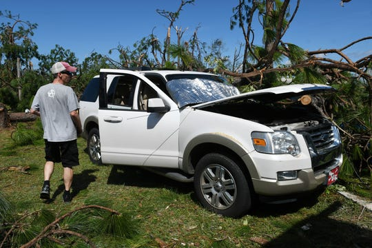 Michael Brown of Panama City cleans up around his truck after Hurricane Michael dropped a tree on it. Mandatory