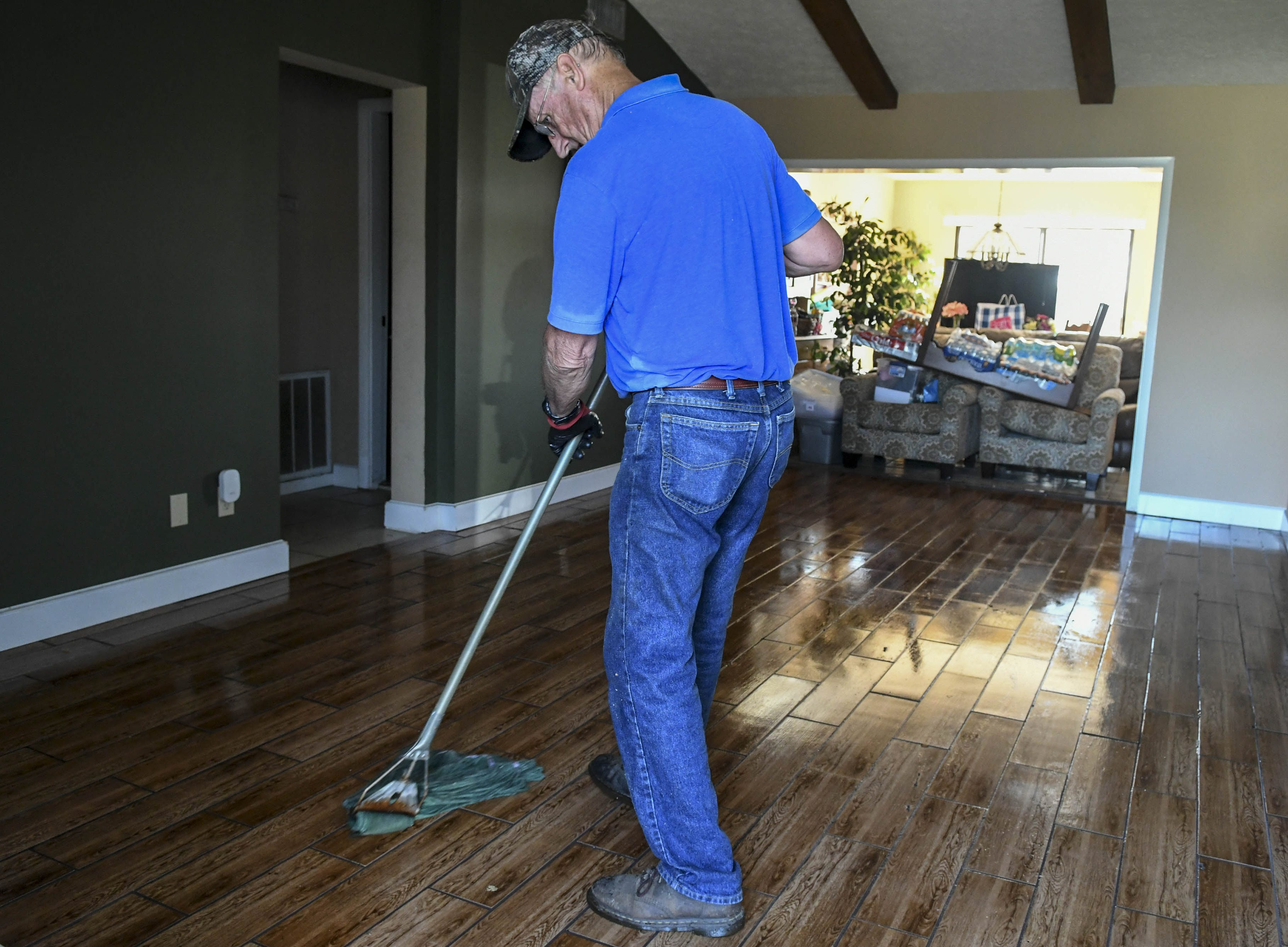 Jim Hankins, pastor of Calvary Baptist Church in Panama City mops up water in his living room Thursday.  Hurricane Michael tore off part of their roof, flooring the home. Hankins was once pastor at Parkway Baptist Church in Merritt Island.
