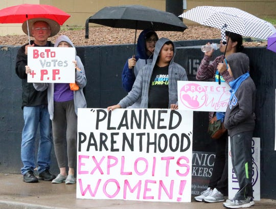 People line the 1500 block of East Missouri Avenue on Friday to protest the opening of a Planned Parenthood health clinic later this month.
