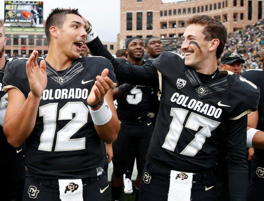 Colorado quarterback Steven Montez, left, jokes with quarterback Josh Goldin as they sing the school song after the second half of an NCAA college football game against Arizona State Saturday, Oct. 6, 2018, in Boulder, Colo. Colorado won 28-21.