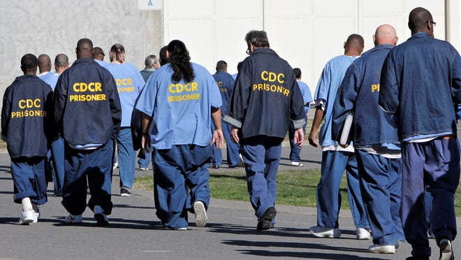 In this Feb. 26, 2013, file photo, inmates walk through the exercise yard at California State Prison Sacramento, near Folsom. The federal receiver who controls medical care in California state prisons is seeking up to a quarter-billion dollars annually to provide medication designed to stem a record increase in fatal drug overdoses among inmates.
