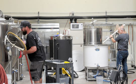 Jesse Johnson, left, cleans the fermenter while his father, Mike Brown, makes a batch of blonde ale at Flat Fish Brewing Co. which shares an address with Cantara Cellars in Camarillo. The brewery, which started serving its beers in May, and the winery, which launched in 2007, will both participate when the Star's Wine & Food Experience takes place Nov. 10 at the Camarillo Airport.