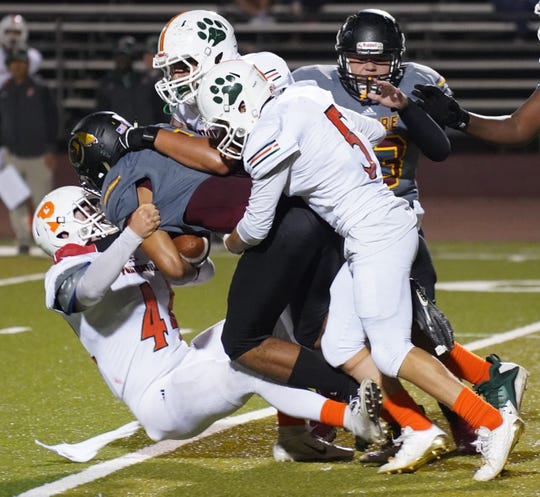The Porterville defense makes a stop against Tulare Union during their football game on Thursday at Bob Mathias Stadium in Tulare.