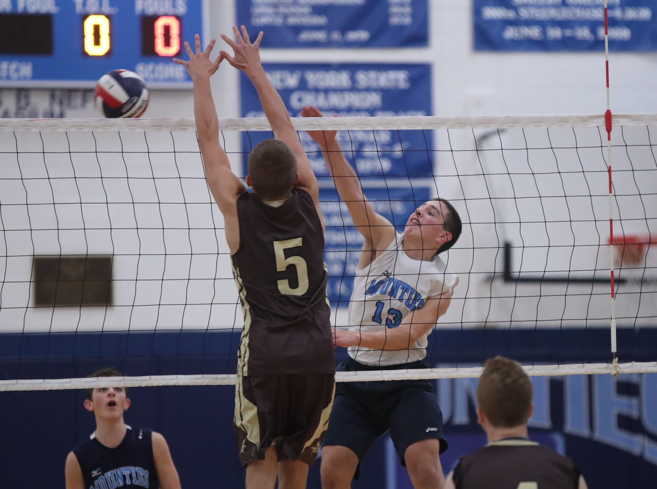 Suffern's Will Kempf (13) hits a shot as Clarkstown South's Trevor Montana (5) attempts a block during their 3-1 win in boys volleyball action at Suffern High School in Suffern on Thursday, October 11, 2018.