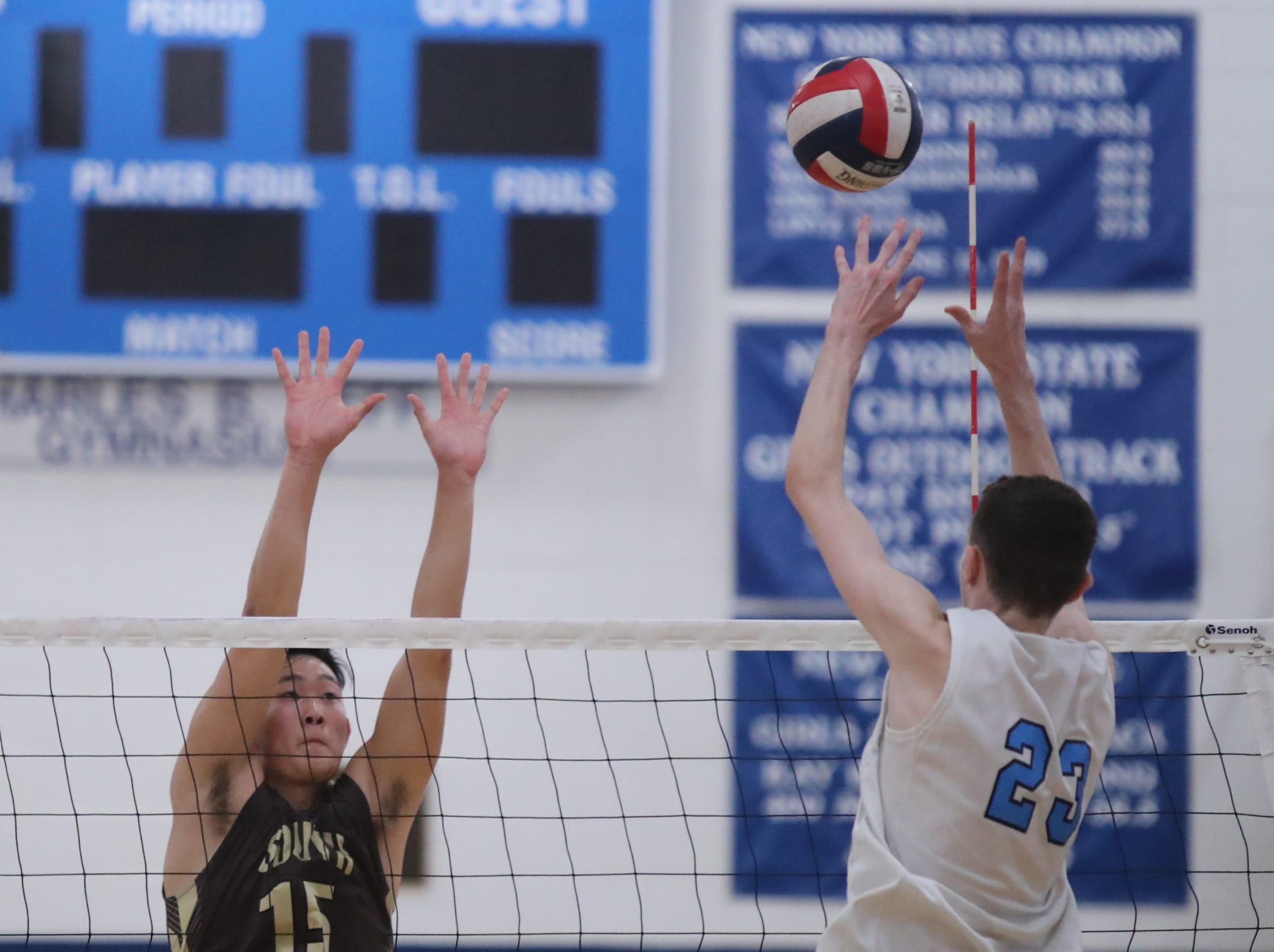 Suffern's Aidan Anderson (23) hits a shot as Clarkstown South's Michael Ro (15) attempts a block during their 3-1 win in boys volleyball action at Suffern High School in Suffern on Thursday, October 11, 2018.