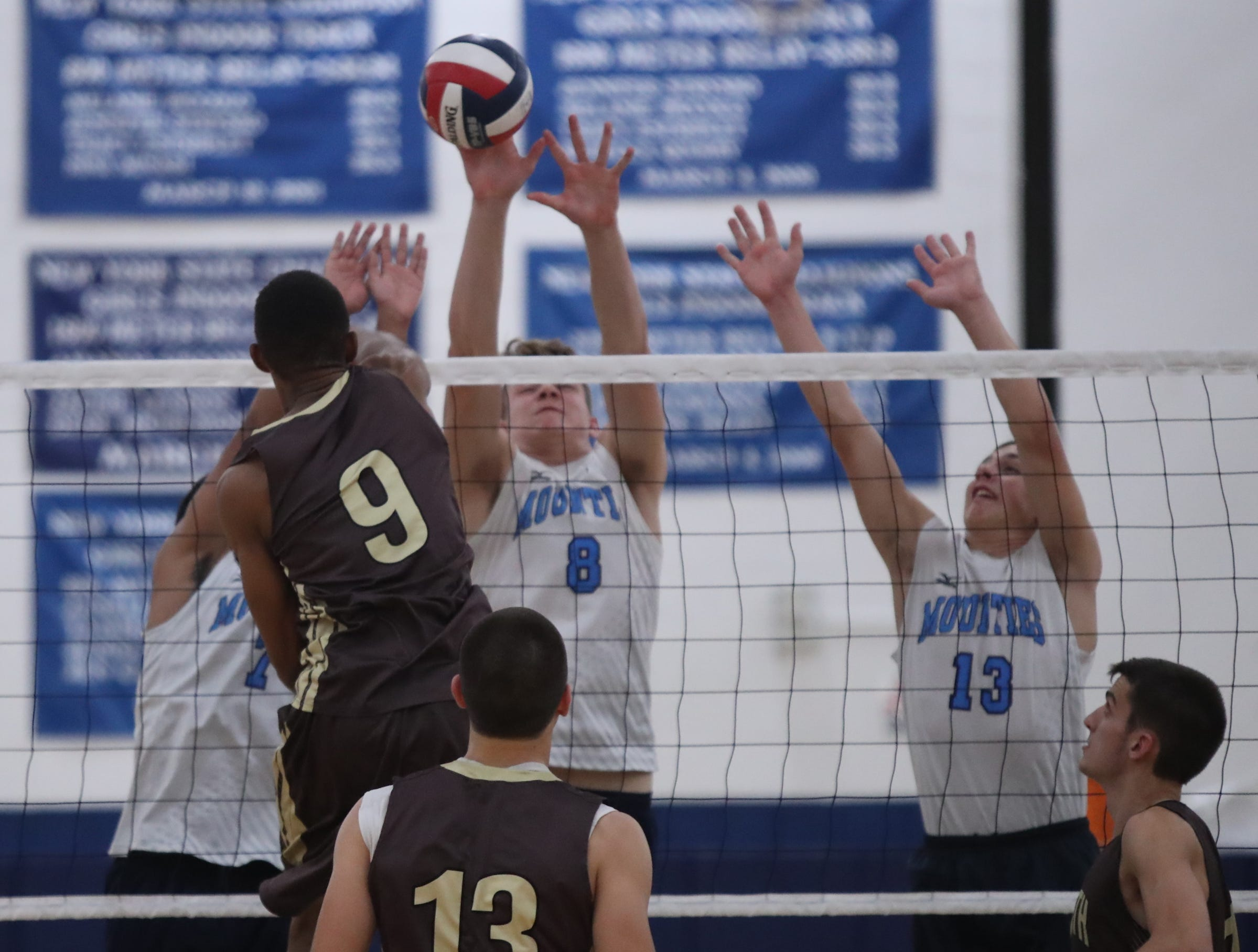 Suffern's Danny Kenny (8) gets a block as Clarkstown South's Fisher Miles (9) comnects with a shot during their 3-1 win in boys volleyball action at Suffern High School in Suffern on Thursday, October 11, 2018.