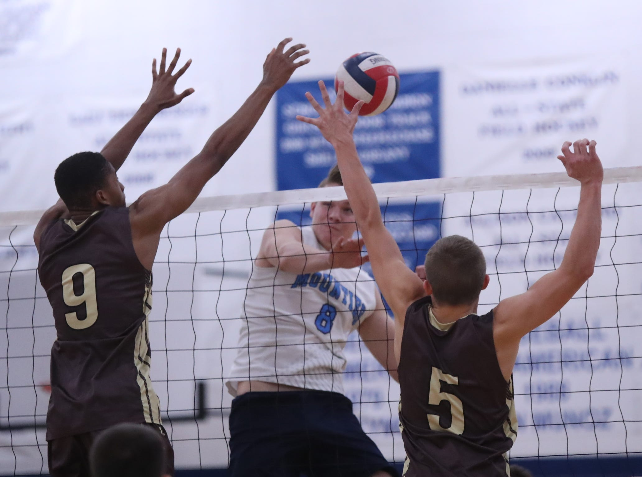 Suffern's Danny Kenny (8) hits a shot in between Clarkstown South's Fisher Miles (9) and Trevor Montana (5) during their 3-1 win in boys volleyball action at Suffern High School in Suffern on Thursday, October 11, 2018.