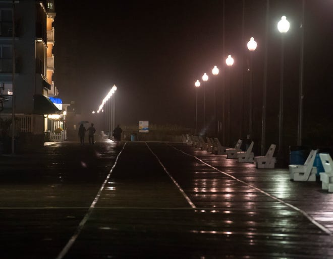 Beachgoers walk on a wet boardwalk at Rehoboth Beach as weather from Tropical Storm Michael moves up the East Coast and into Delaware.