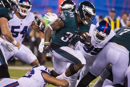 Eagles' Corey Clement (30) breaks through the Giants defense Thursday at MetLife Stadium.