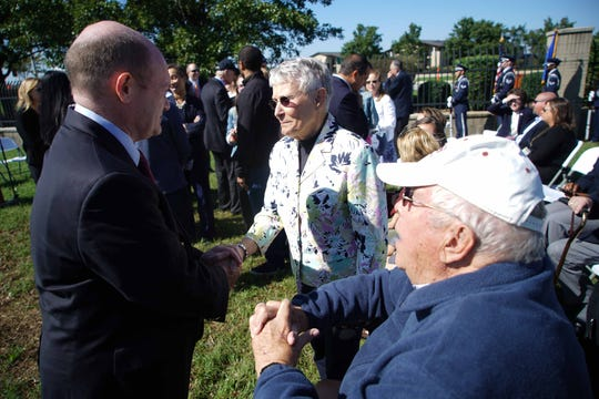 Sen. Chris Coons shakes hands with Sr. Airman Elizabeth Loncki's grandparents Cindy and Dave Koski, before a bridge dedication ceremony at the Dover Air Force Base on Friday afternoon.
