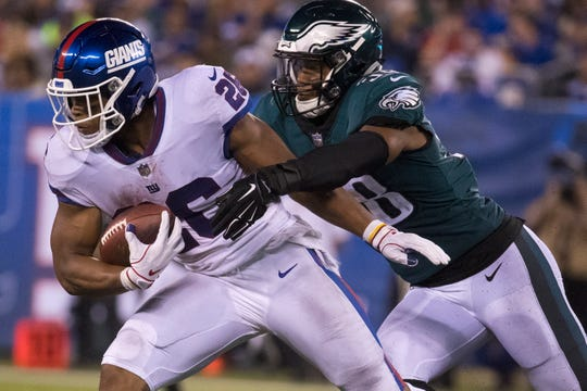 Eagles Jordan Hicks (58) reaches out to wrap up New York's Saquon Barkley (26) in the Eagles' 34-13 win on Oct. 11.