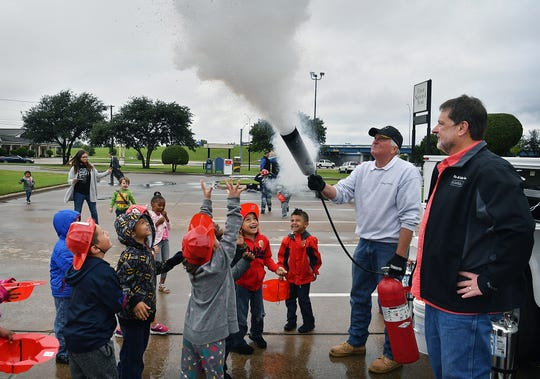 Ben Crabb, right, and Mark Toby of Fire & Safety Inc. demonstrate a CO2 fire extinguisher for Lamar Elementary kindergarten students Friday monring at First National Bank. The bank hosts a fire safety session for the children each year during Fire Safety Week.