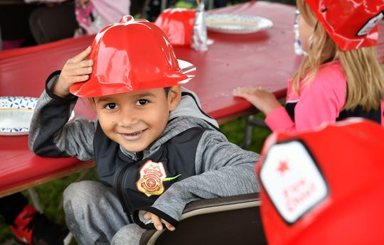 Anthony Gonzales, a Lamar Elementary kindergartener, shows off his badge and fire helmet that he and his classmates got during a fire safety field trip Friday at First National Bank.