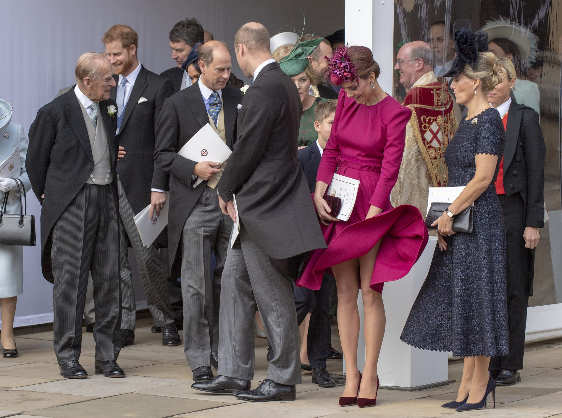 Hold that dress down Kate! Queen Elizabeth II, Prince Philip, Duke of Edinburgh , Prince Harry, Duke of Sussex, Prince Edward, Earl of Wessex, Prince William, Duke of Cambridge, Catherine, Duchess of Cambridge and Sophie, Countess of Wessex attend the wedding of Princess Eugenie of York to Jack Brooksbank, Friday.