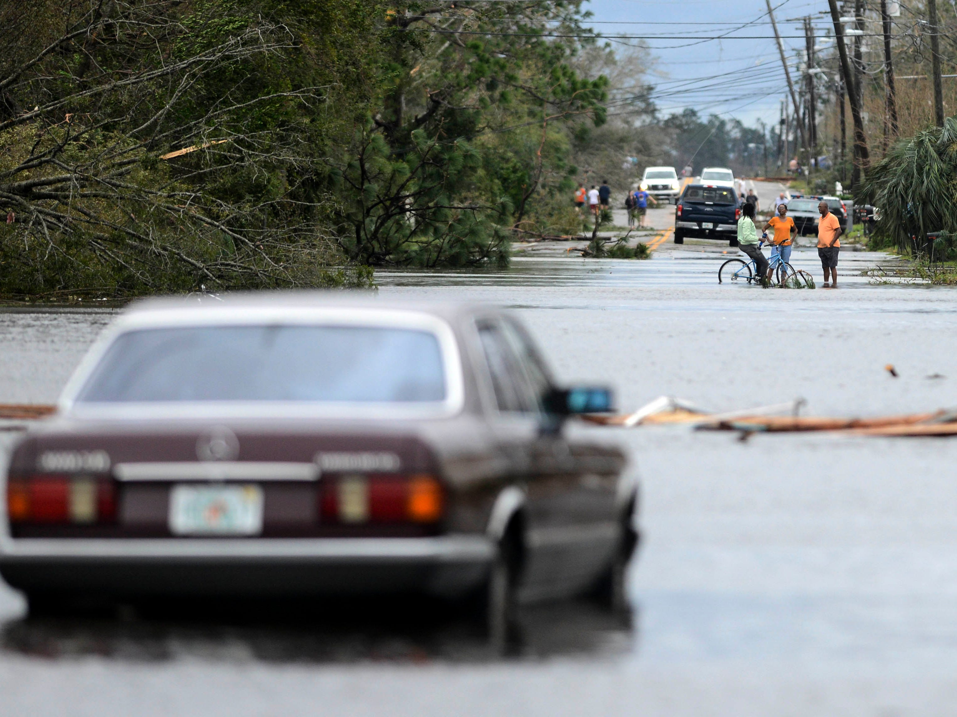 People stand in a flooded street in Panama City, Fla Oct. 11, 2018.