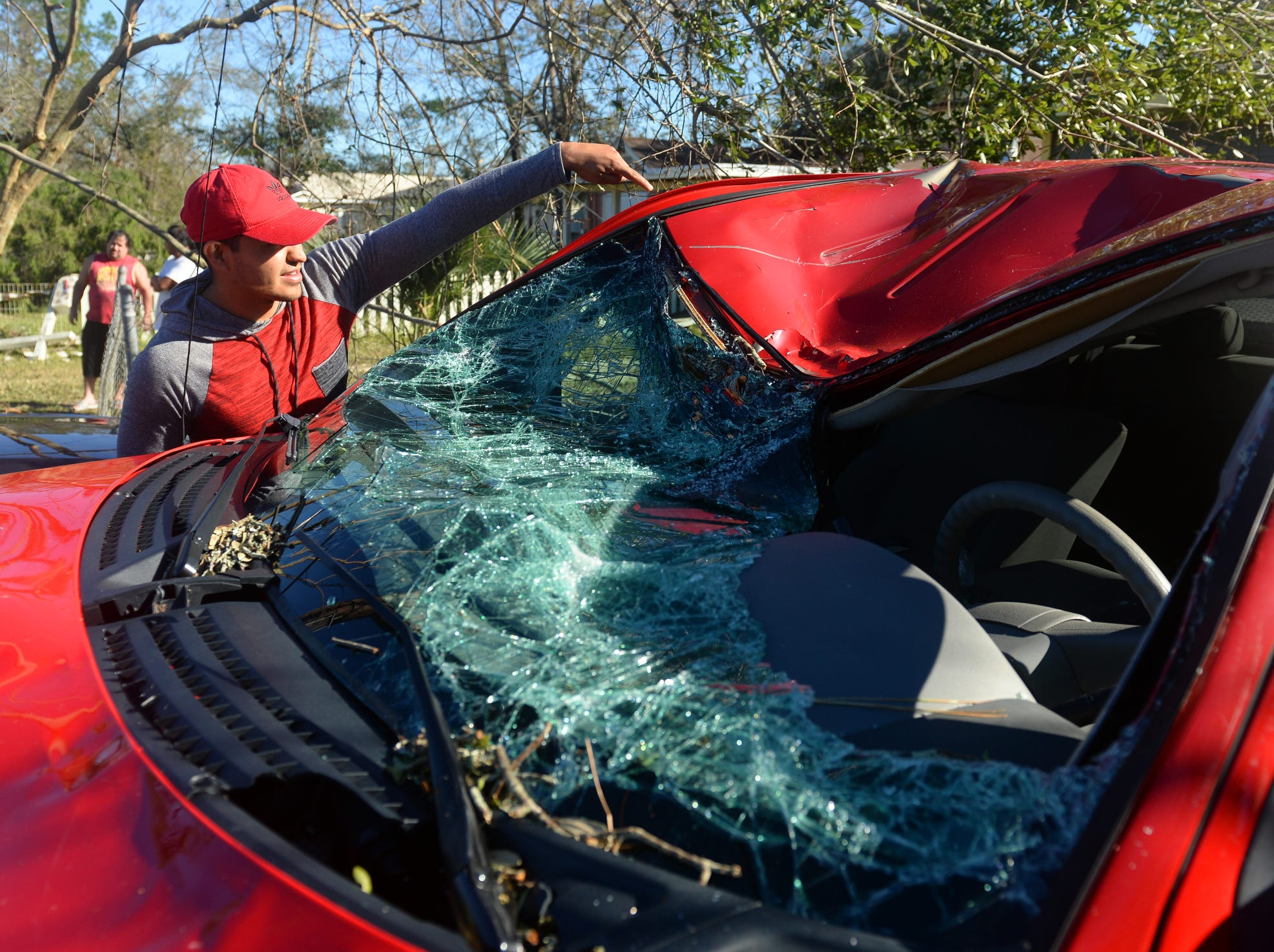 "Alan Cervantes looks over his truck that was smashed by a large tree on his property as a result of the high winds from Hurricane Michael. Cervantes, 22, had moved from Dallas just a year ago. ""I'm mostly worried about continuing to work,"" Cervantes said. ""I might just move back to Texas."""