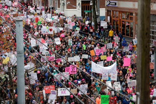 """In this file photo taken on January 20, 2018 people participate in Women's March 2.0, one year after women worldwide marched for women's rights and to protest President Trump's inauguration, in Seattle, Washington. - Energized by a bitter fight over a US Supreme Court justice nominee, thousands of women were expected to march Saturday in Chicago and cast early midterm election ballots against the """"anti-woman agenda"""" of President Donald Trump's administration."""