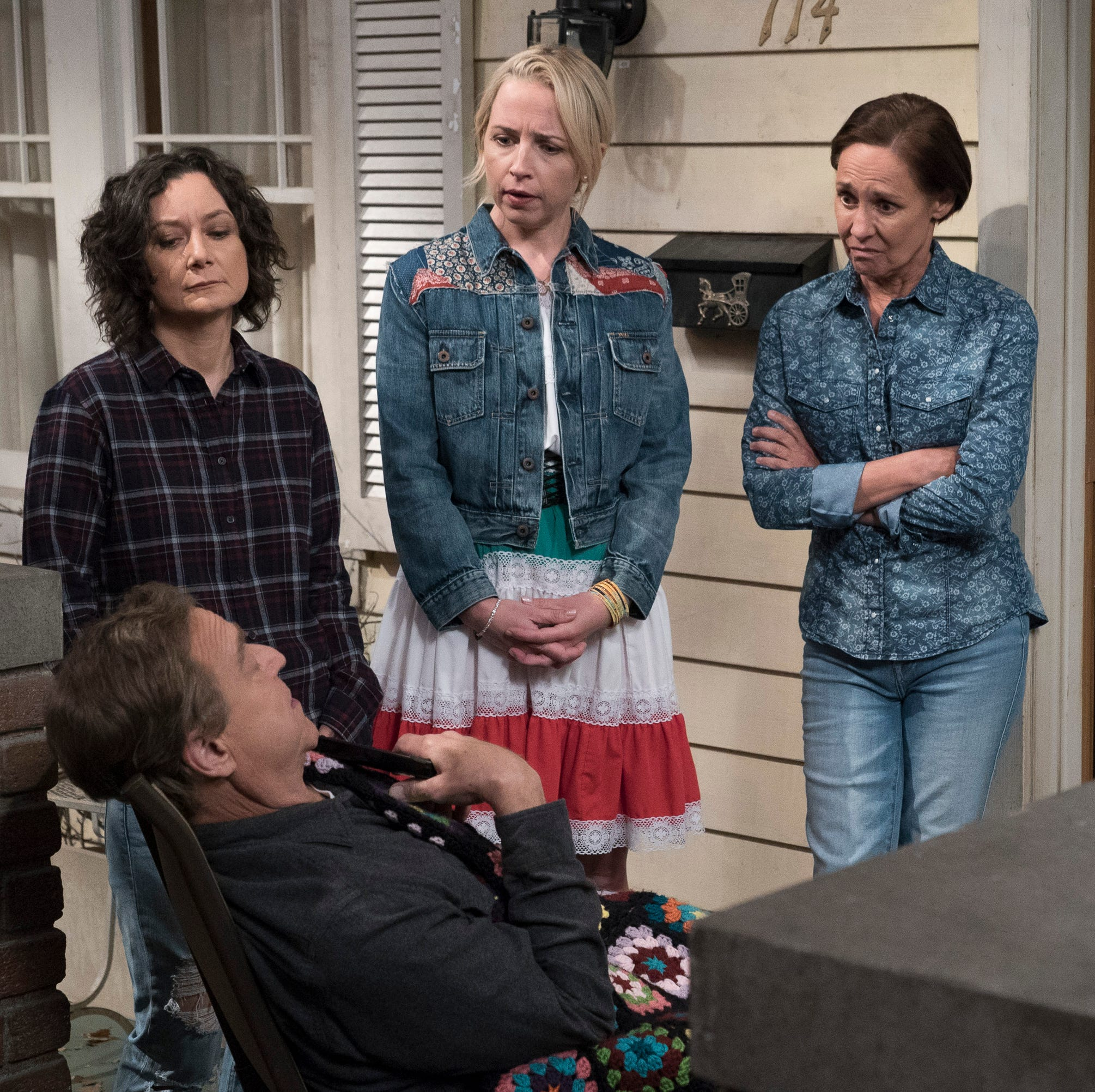Darlene (Sara Gilbert), standing left, Becky (Lecy Goranson) and Jackie (Laurie Metcalf) observe Dan (John Goodman), front left), in ABC's 'The Conners.'