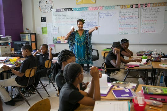 Felecia Branch talks about hitting the bullseye as she teaches a sixth-grade class at Mackenzie Elementary-Middle School in Detroit.