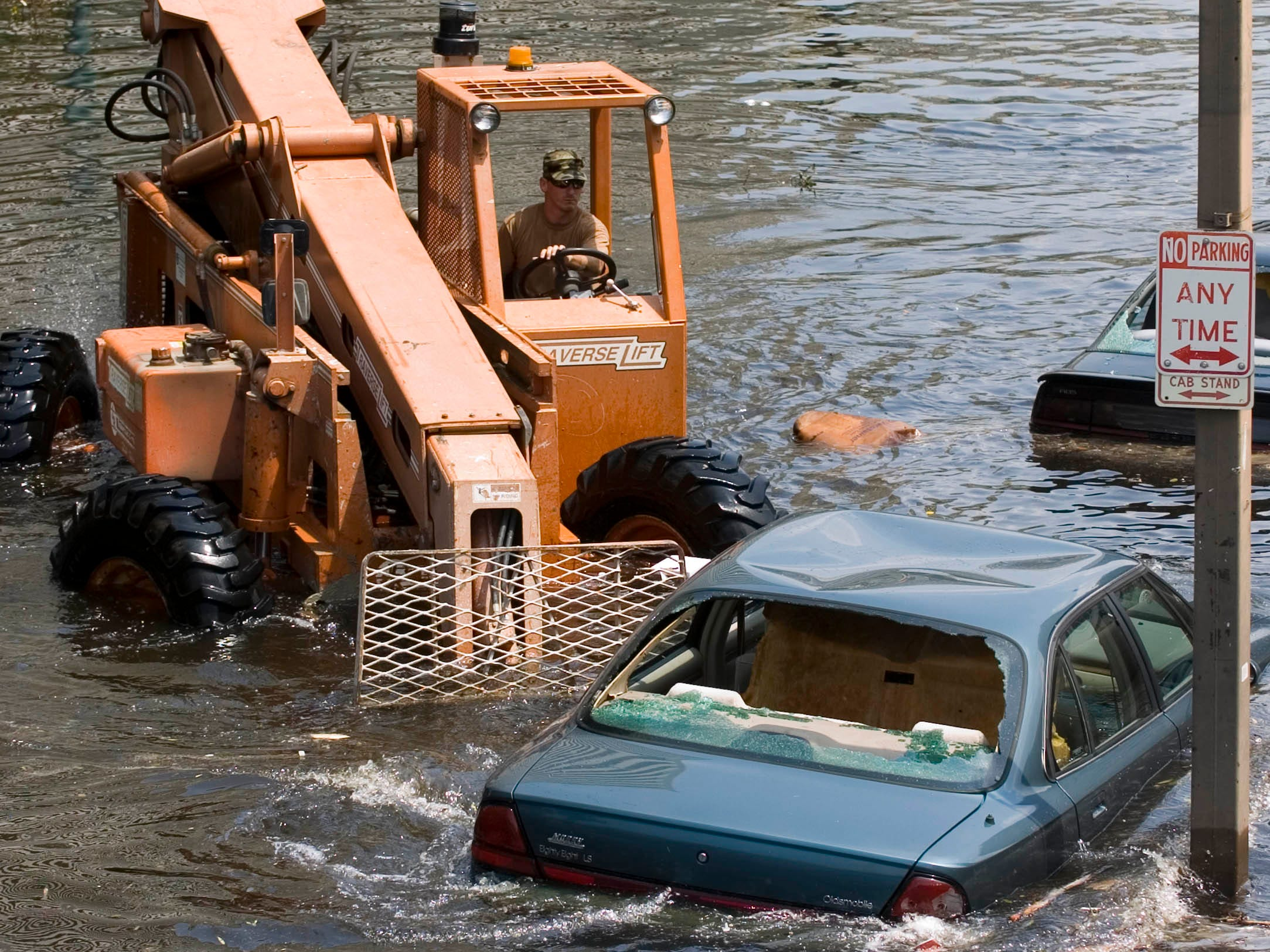 A soldier with the LA Army National Guard uses a forklift to push abandoned vehicle out of the path of rescue vehicles during the aftermath relief effort of Hurricane Katrina, August 31, 2005, in New Orleans, LA. (M. Scott Mahaskey/ Army Times)