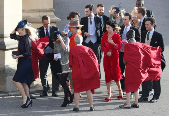 Chelsy Davy, left, and other guests hold their hats in the wind when they arrive for the wedding of Princess Eugenia of York and Jack Brooksbank in the Chapel of St. George, Windsor Castle, on October 12, 2018.