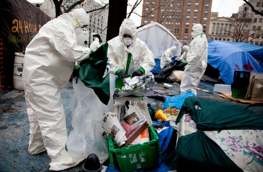 Workers in protective gear remove tents, camping gear and debris left by Occupy DC protesters in McPherson Square on Feb. 5, 2012, in Washington.