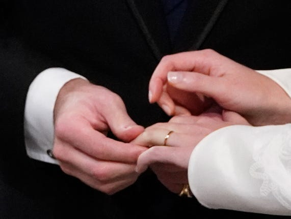 The groom Jack Brooksbank places a wedding band on the finger of his bride, Britain's Princess Eugenie of York.