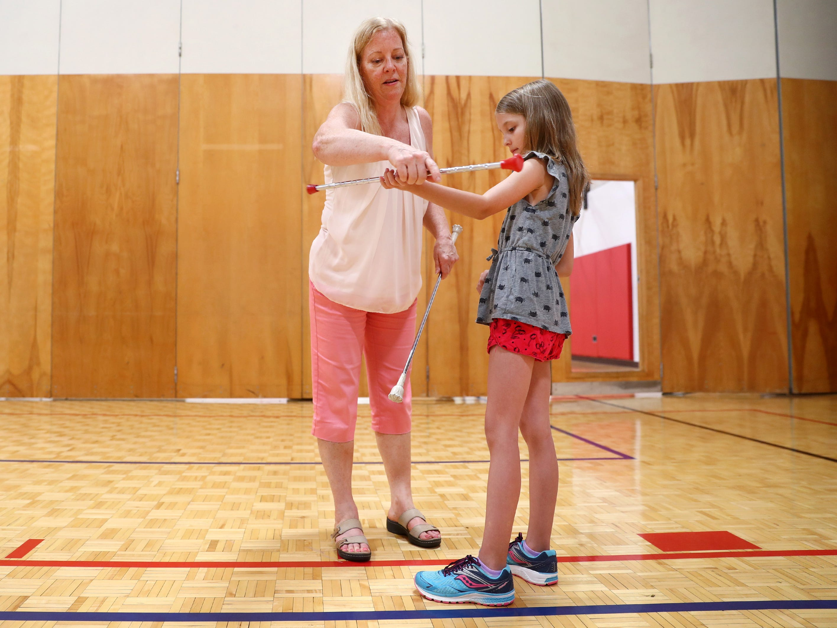 Neenah, WI – Maripat Franke, a special education teacher at Neenah High School currently enrolled in the Residency In Teacher Education 2.0 program at CESA 6, works with Cecelia Preman, 8, while teaching a baton twirling class at the Neenah/Menasha YMCA. Franke teaches the class Monday nights after school.