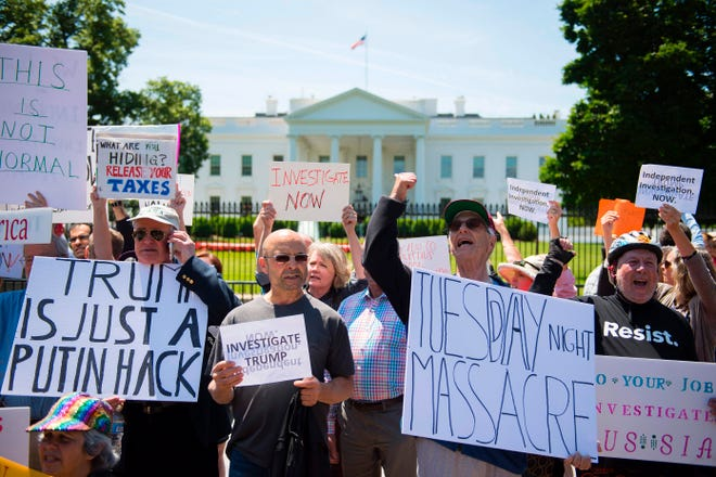 Protesters hold placards and chant in front of the White House during a protest demanding an independent investigation in the Trump/Russia ties after the firing of FBI Director James Comey in Washington, DC, May 10, 2017. / AFP PHOTO / JIM WATSONJIM WATSON/AFP/Getty Images ORG XMIT: Protest i ORIG FILE ID: AFP_OA2KF