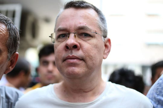 In this file photo taken on July 25, 2018 US pastor Andrew Brunson escorted by Turkish plain clothes police officers arrives at his house on July 25, 2018 in Izmir.