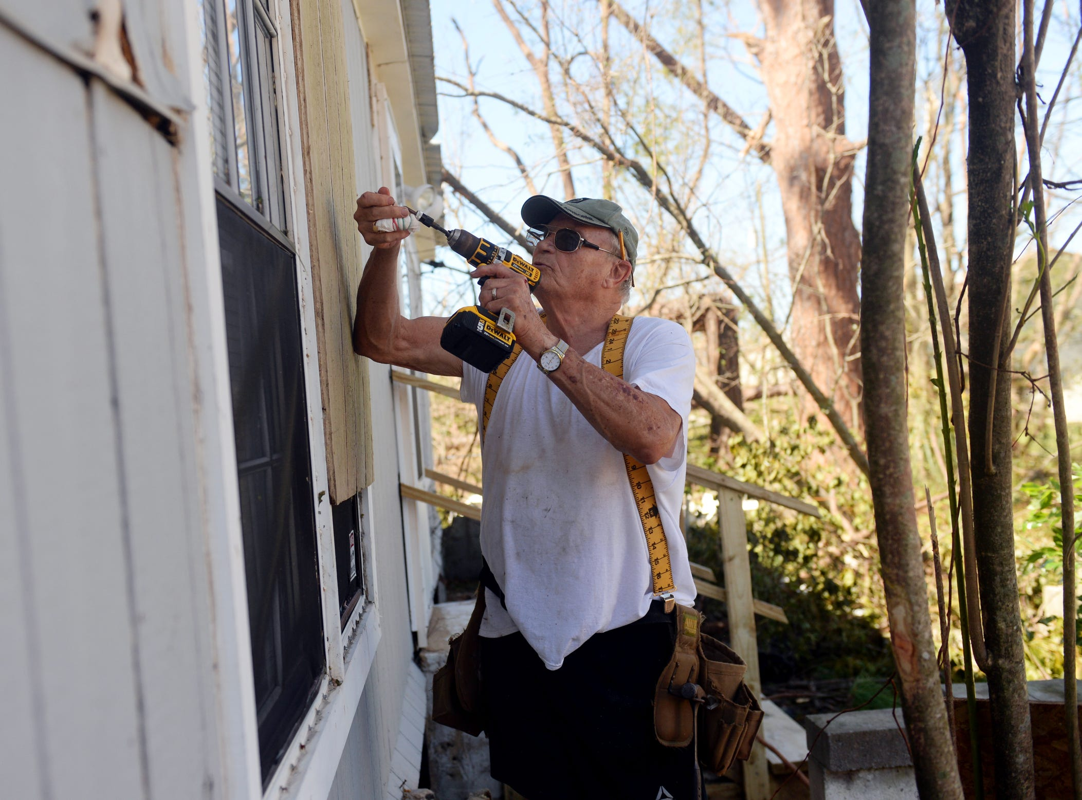 "Clayton Wentworth puts up boards to cover a few of the broken windows of his home after Hurricane Michael blew through the area on Wednesday. Wentworth and his wife, Lucretia, are going to leave the area and wait for the power and water to be turned back on. ""I guess this will be a good time to travel and see some friends around the country,"" Lucretia Wentworth said."