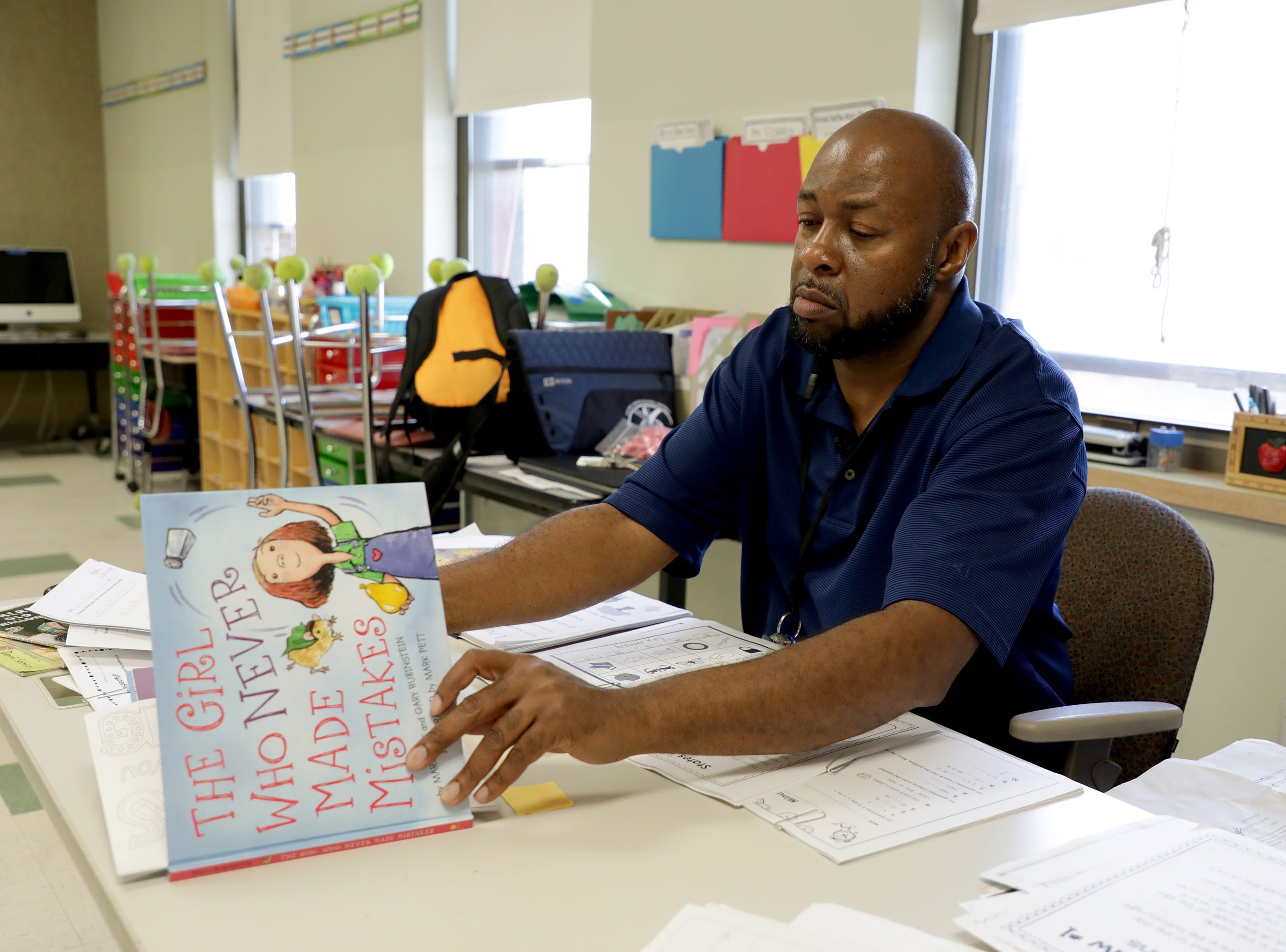 Racine WI – Edward Lawson checks the lesson plans of a second grade class before a substitute teacher arrives.