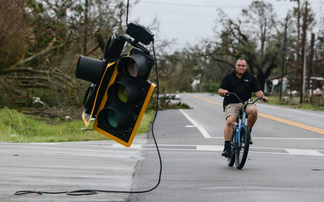 A bicyclist rides past a downed traffic light in Panama City, Florida, after Hurricane Michael.