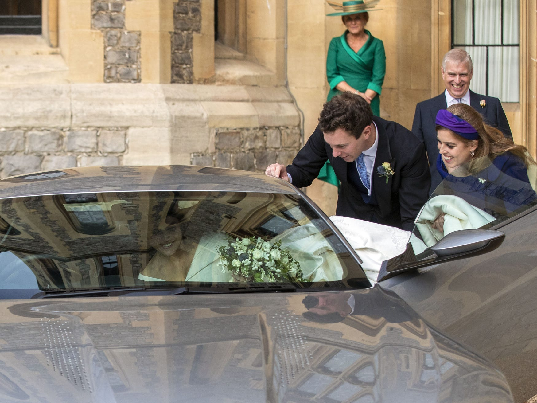 Princess Eugenie and Jack Brooksbank  are helped by Princess Beatrice and Prince Andrew, Duke of York leave Windsor Castle after their wedding for an evening reception at Royal Lodge, in Windsor, England.