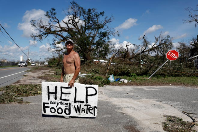 """Michael Williams, 70, looks for help from passing motorists for food and water as downed trees prevent him from driving out of his damaged home in the aftermath of hurricane Michael with his family in Springfield, Fla., Oct. 11, 2018. """"I don't know what I'm going to do,"""" said Williams."""