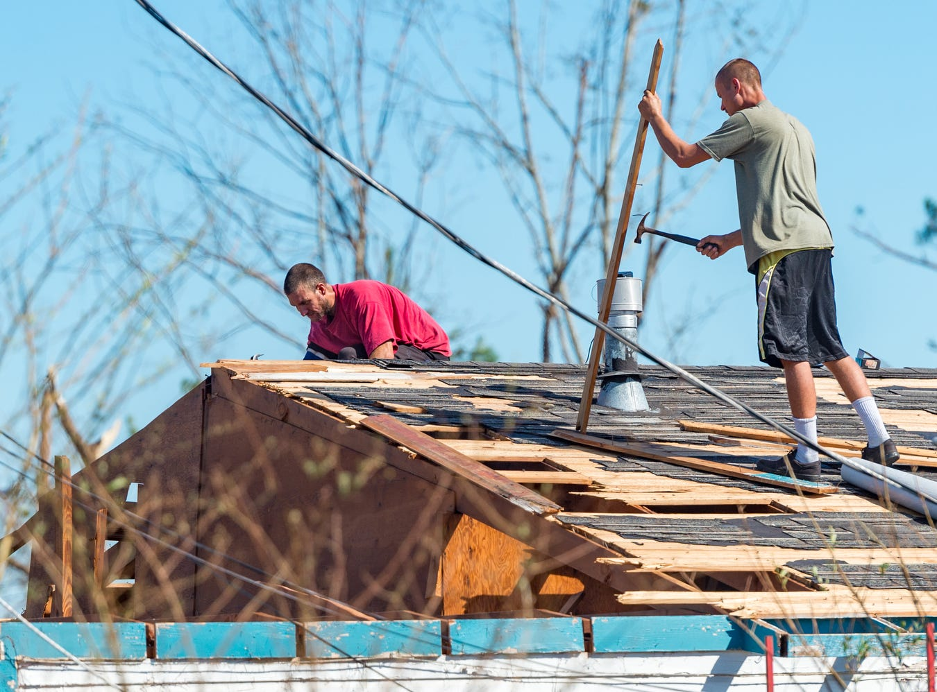 Panama City, Fla. residents work to repair a roof damaged by Hurricane Michael, Friday.