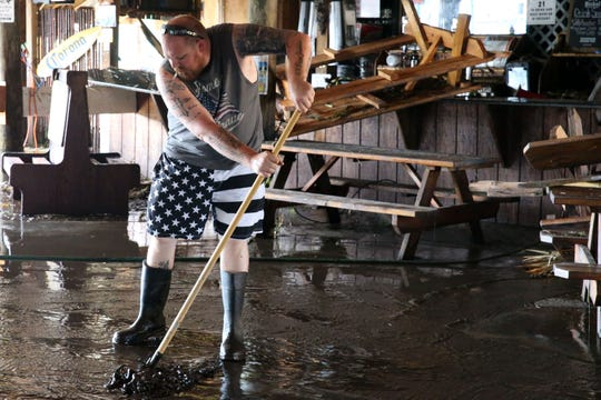 Riverside Cafe employees clean up river sludge that filled the restaurant after Hurricane Michael tears through the panhandle in St. Marks, Fla.