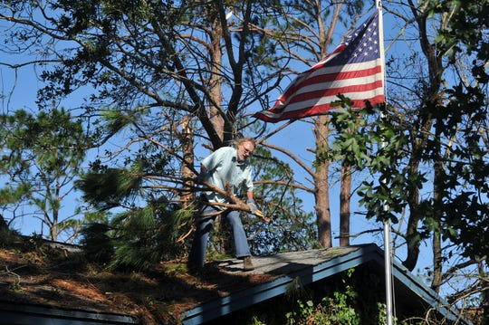 "Wayne Mann works to clear debris left from Hurricane Michael from the roof of his home in Panama City. ""We were sitting in the house just listening to the storm and all of a sudden there was a loud crash and water started coming through eh ceiling in the bedroom,"" said Mann's wife, Jeanette."
